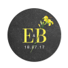 Autocollant rond avec le logo des mariés composé de leurs initiales et de fleurs à l'aquarelle.