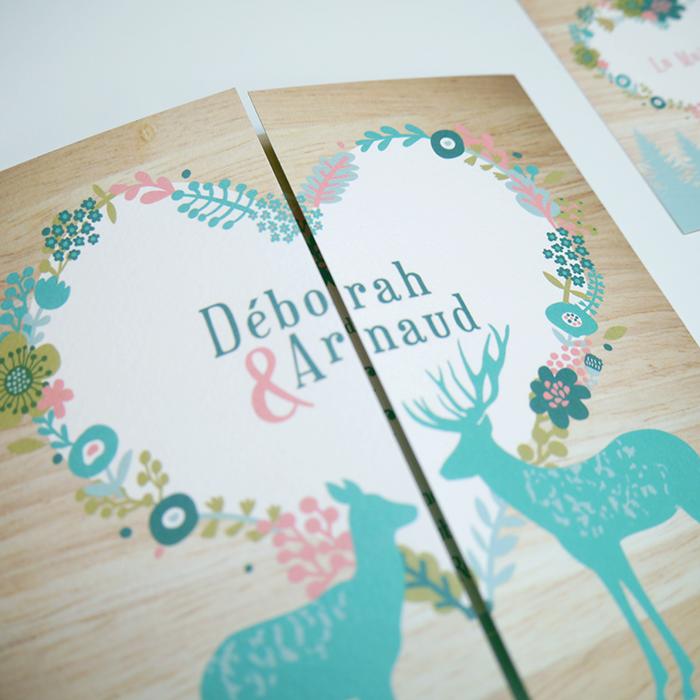Faire-part de mariage montagnard, coeur avec couronne de fleurs, cerf et biche sur fond bois.