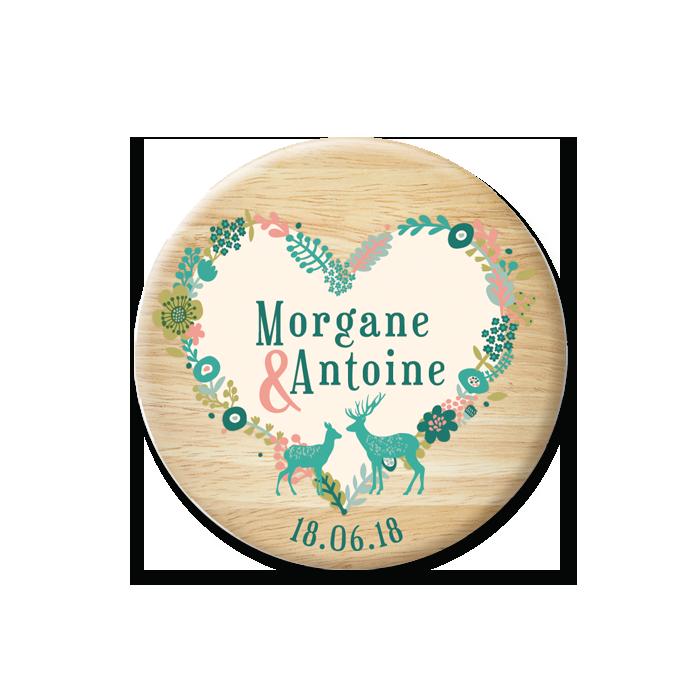 Save the Date de mariage Montagne, fond bois et cerfs sur un coeur formées de fleurs illustrées.